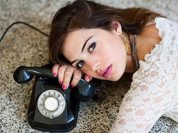 The girl is waiting for the phone call from her loved one.